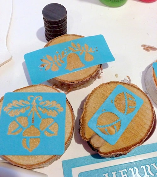 Adhesive stencils attached to wood slices