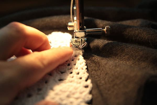 Sewing a doily onto the front of a t-shirt with a sewing machine