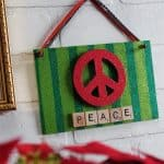 This holiday sign uses some of my favorite craft supplies - scrabble tiles, glitters, and the peace symbol. It's the perfect holiday display!