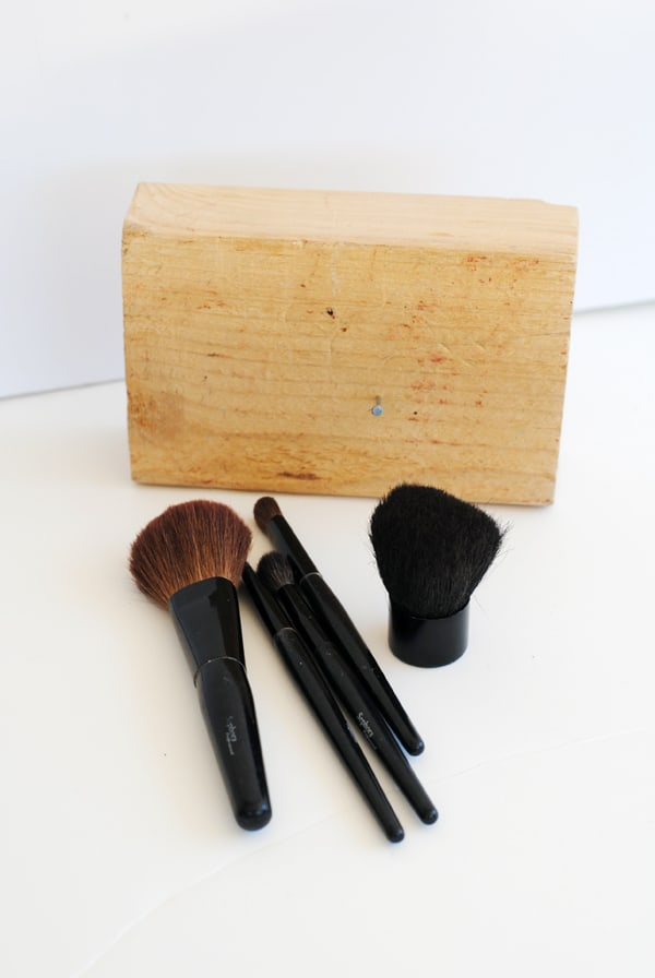 a block of pine wood and several makeup brushes
