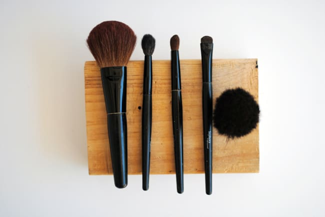 Makeup brushes laid out on a block of wood