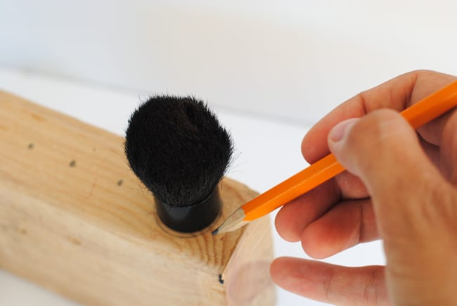 Trace the base of a kabuki makeup brush with a pencil onto a block of wood