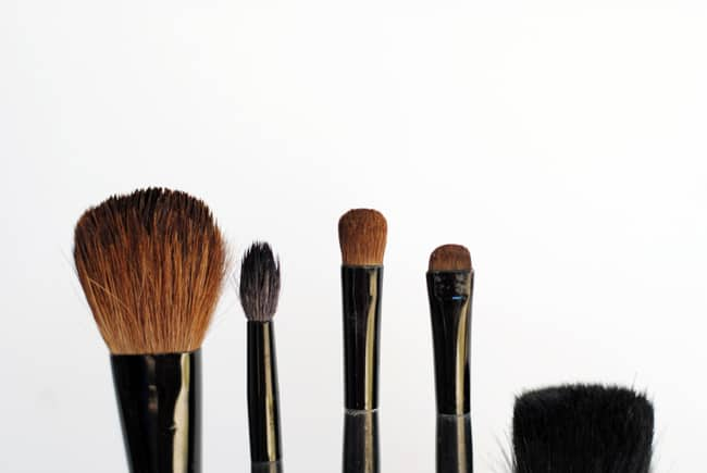 The tops of makeup brushes at various heights