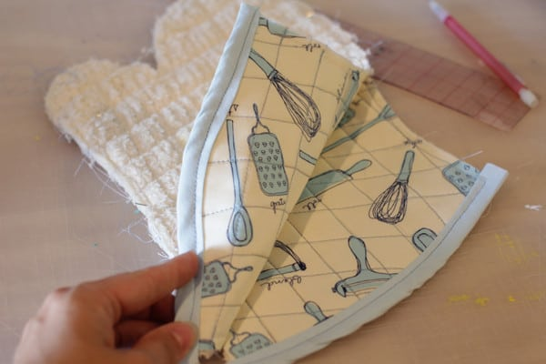 Sew bias tape onto the bottom of the two quilted fabric pieces