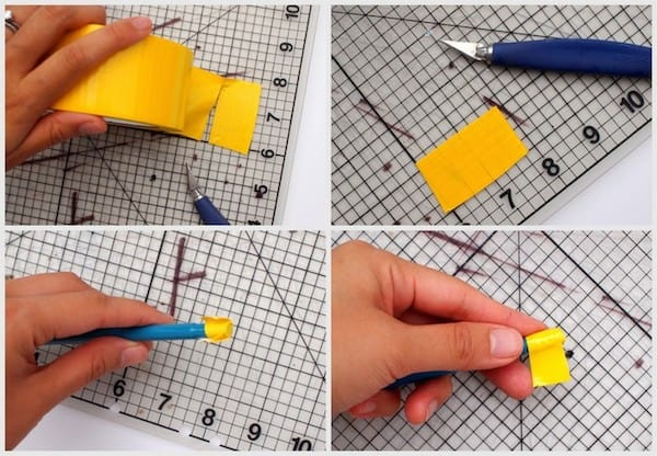 Yellow duct tape being rolled onto the end of a pen