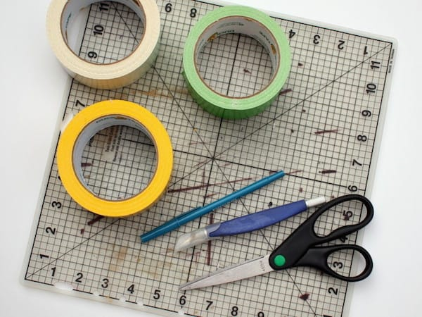 Rolls of duct tape sitting on a craft mat with scissors, a pen, and a craft knife