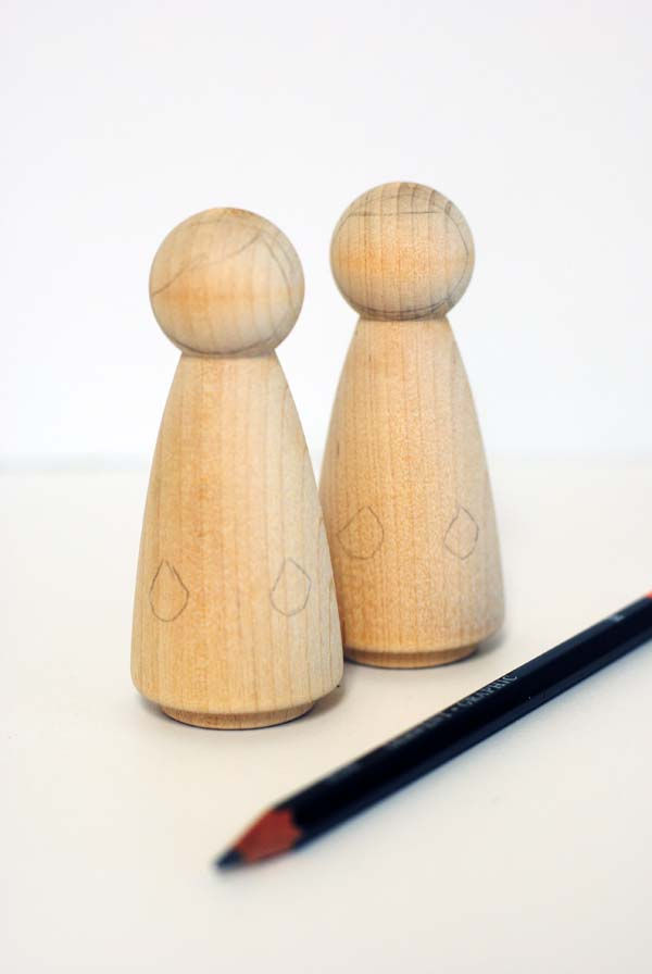 Drawing on wood peg dolls with a pencil