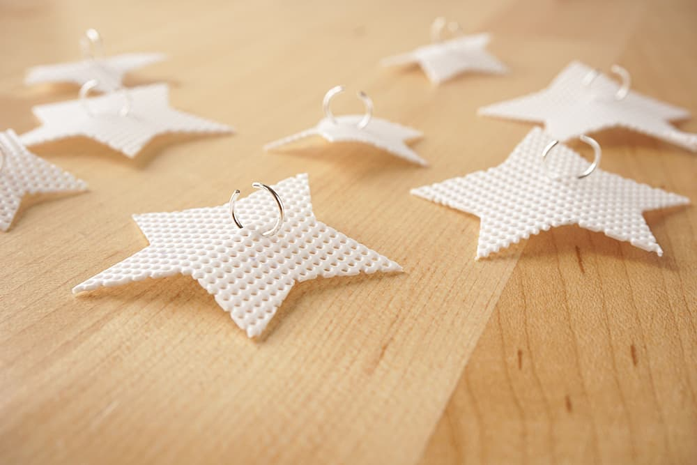 This holiday craft is a twist on standard lights - add plastic canvas star DIY Christmas light covers to make them look super cool and modern! Perfect for your winter wonderland.