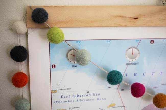 Detail shot of a felt ball garland on a map