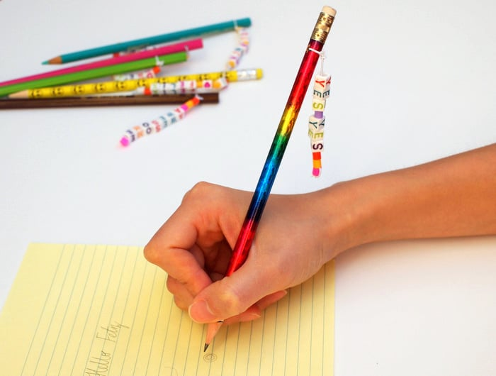Child writing with a personalized pencil on a yellow piece of paper