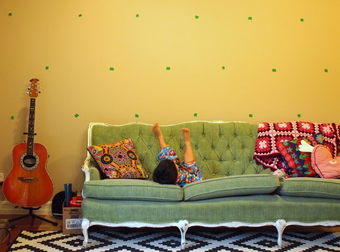 Masking tape marks on the wall with a green couch and guitar
