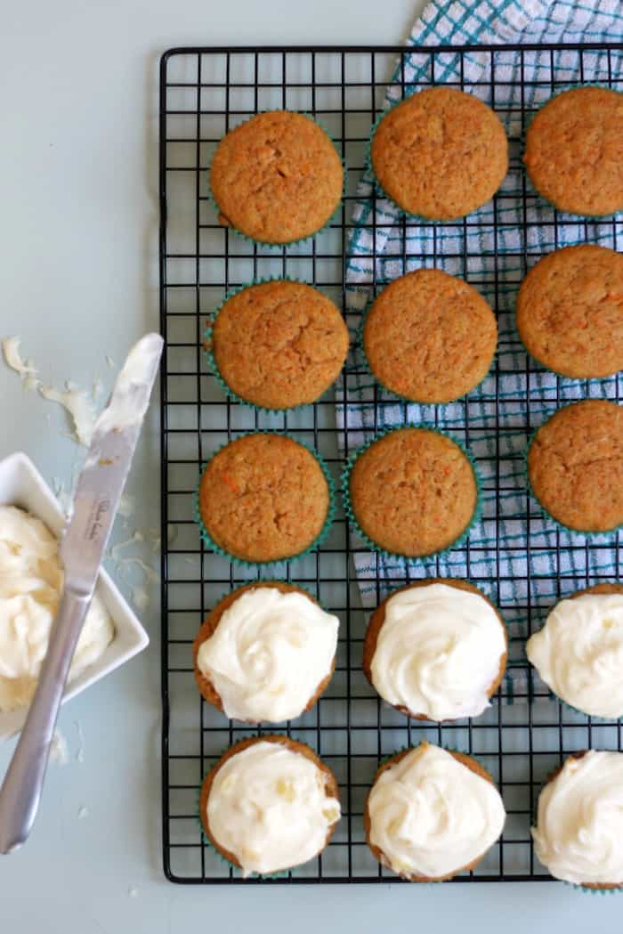 Spreading cream cheese icing on carrot cake muffins