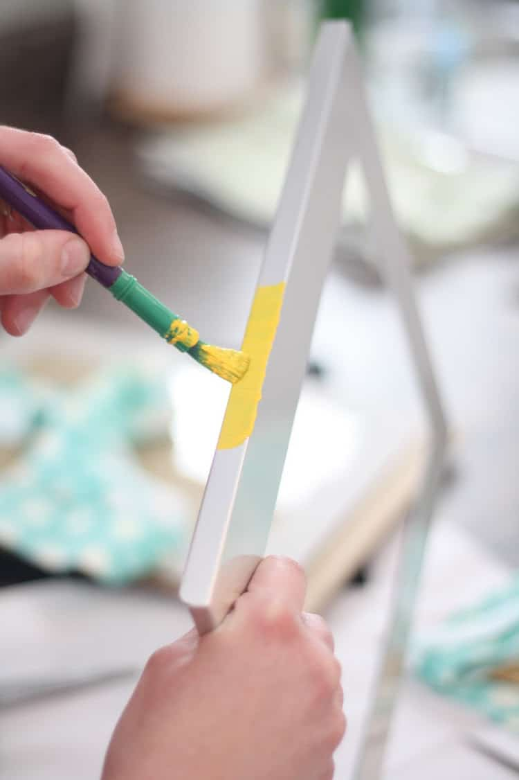 Woman painting the edges of a picture frame