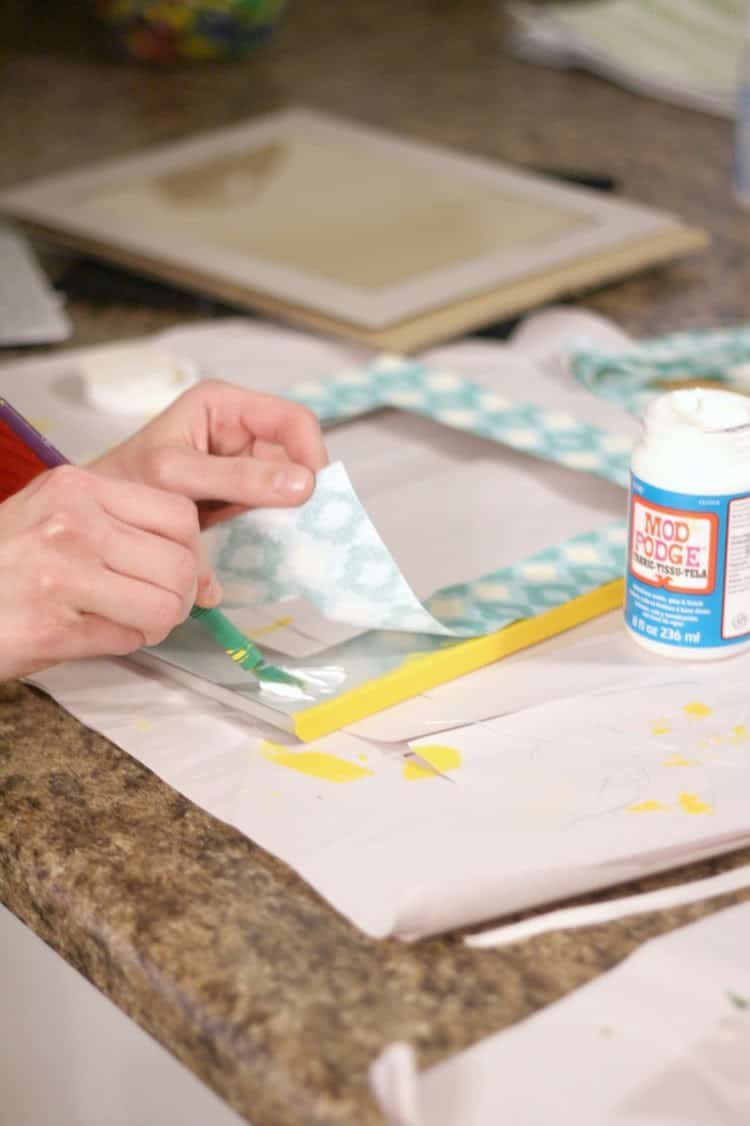 Adding Mod Podge to the frame with a paint brush