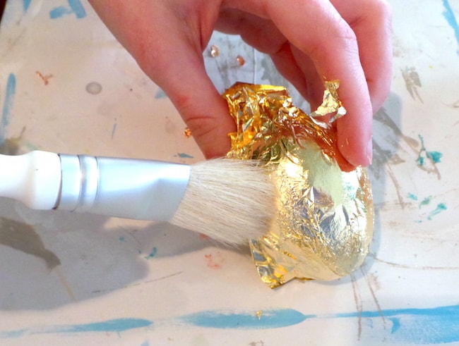 Add gold leaf to a painted wood Easter egg