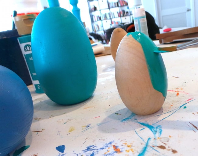 Painting a wood Easter egg with aqua acrylic paint