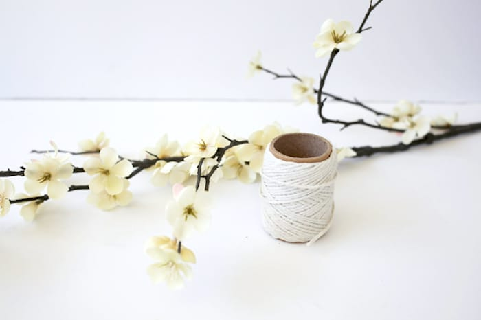 Faux flowers on a branch and roll of twine