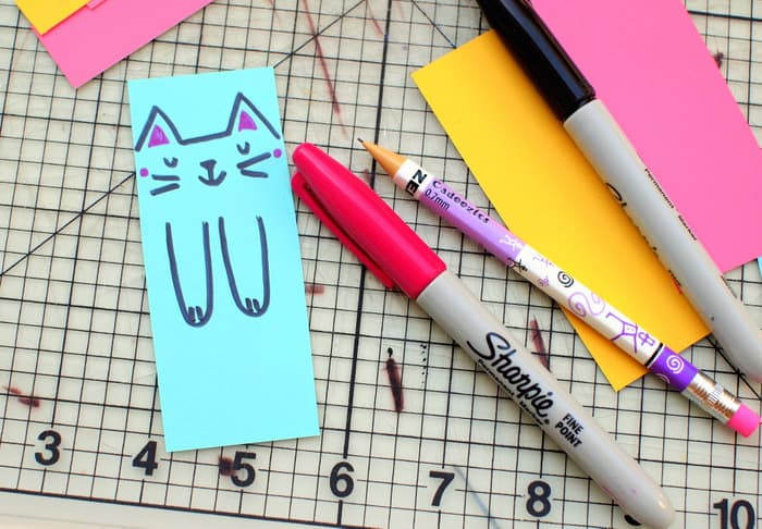 Draw a cat face on a paint chip with pink and black Sharpies