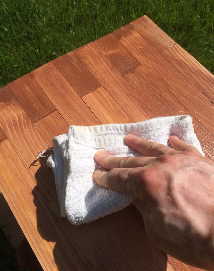 Applying brown stain to a DIY outdoor bench with a white rag
