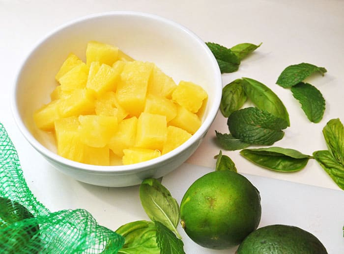 Cut pineapple chunks in a bowl and lime