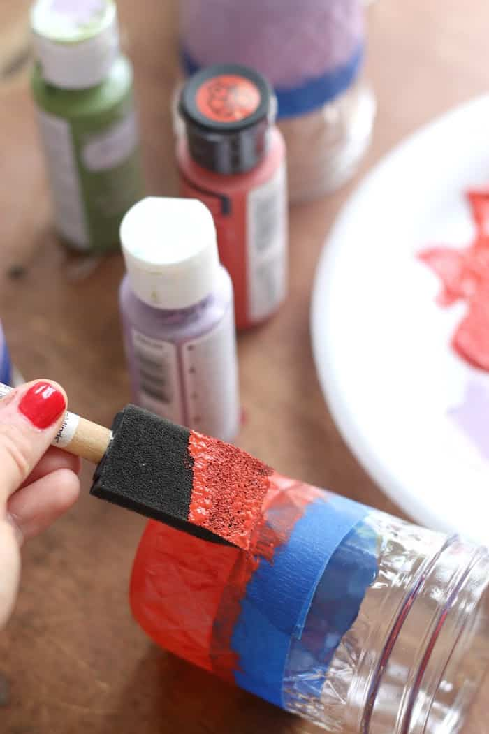 Painting a mason jar with red acrylic paint and a foam brush