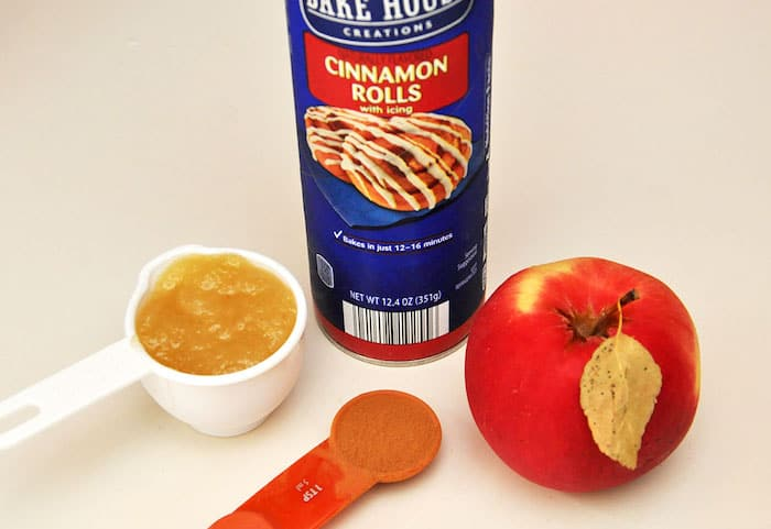 Can of cinnamon rolls, applesauce, and an apple