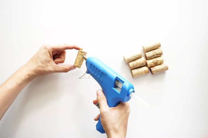 Placing a bead of hot glue down a cork with a hot glue gun