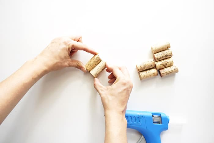 Two hands pressing two corks together with hot glue