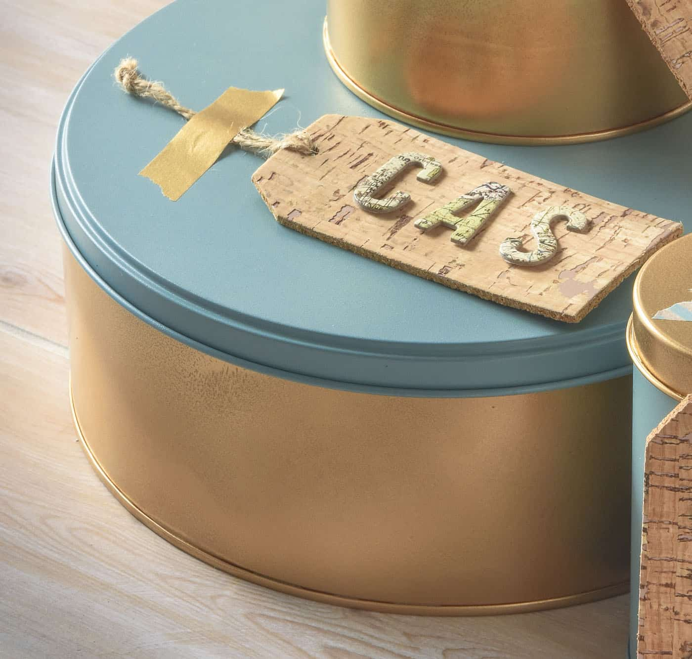 Use spray paint to revive and upcycle old Christmas tins! Add cork tags and adhesive letters to use them for gift containers or storage. So easy!