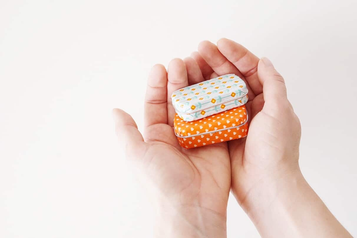 Altoid tins covered in washi tape sitting stacked in someone's hands