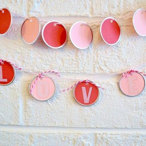Use metal rimmed tags from the craft store to make a pretty DIY garland in minutes! Perfect for Valentine's Day or any other holiday - no skills required.