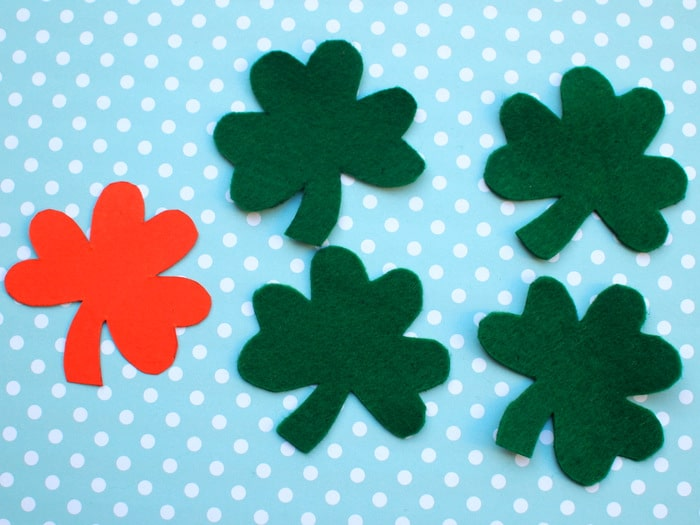 Four shamrock shapes cut out of green felt