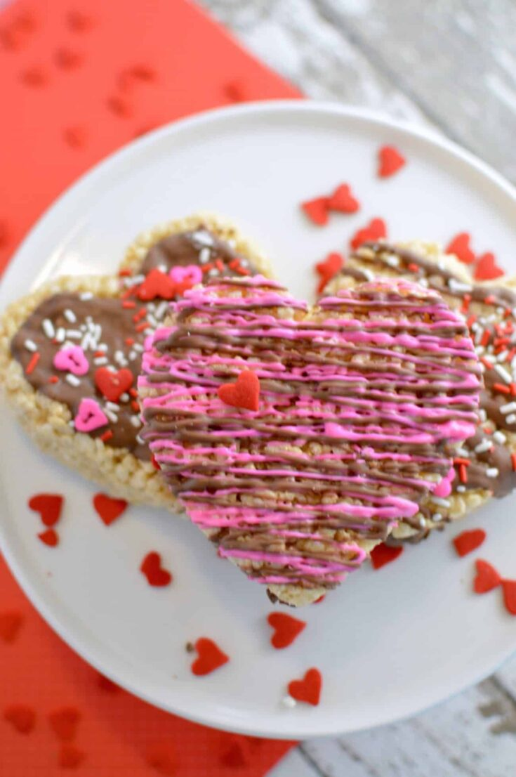 This Rice Krispie treat recipe is made extra awesome for Valentine's Day with the heart shape and the addition of chocolate drizzle and sprinkles. So fun!