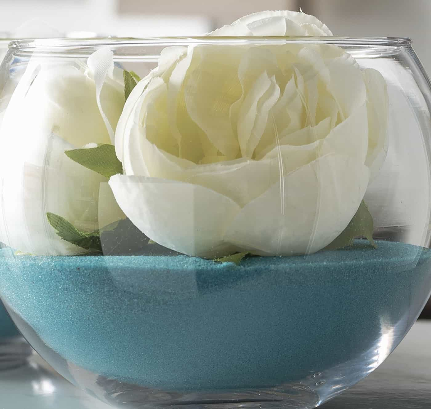 Cheap diy wedding centerpieces using craft sand, faux flowers, and glass bubble bowls