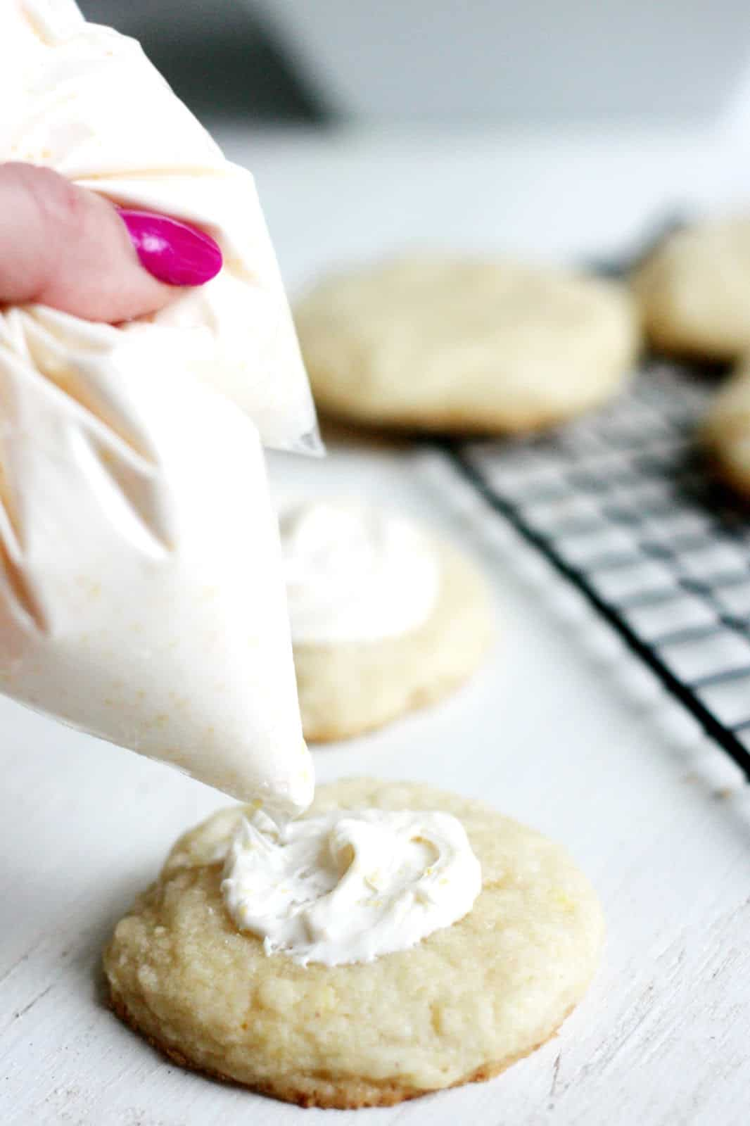 Spreading cream cheese icing on the top of a lemon cookie