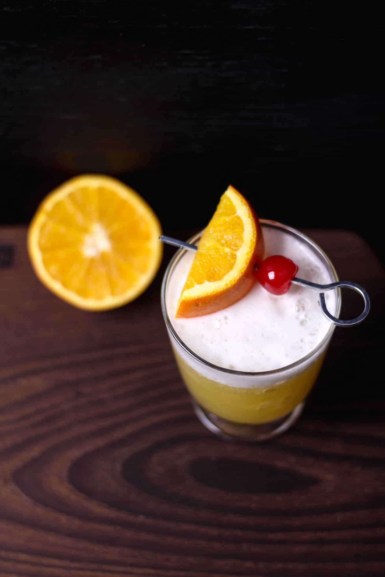 This delicious whiskey sour recipe goes down so easily! Flavored with orange juice and topped with whipped cream and a cherry, it's a tasty cocktail treat.