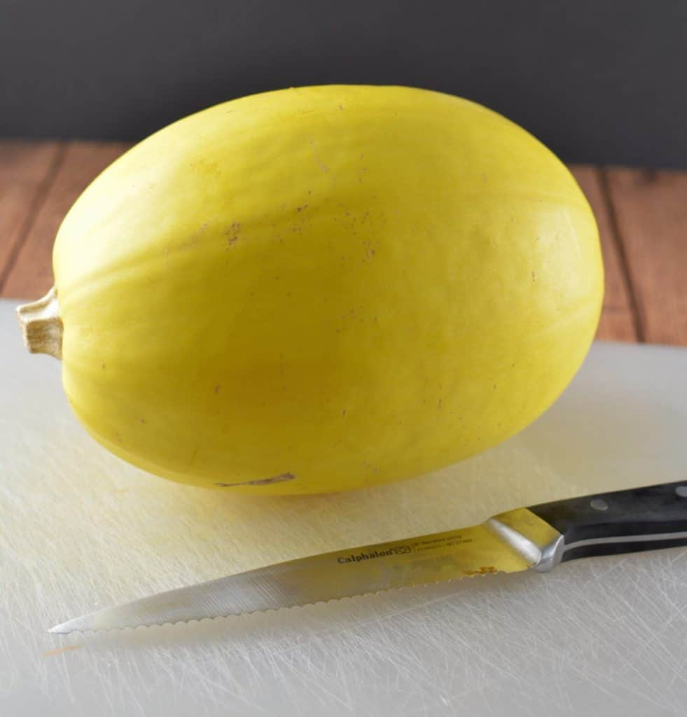 Spaghetti squash sitting on a white cutting board with a Calphalon knife