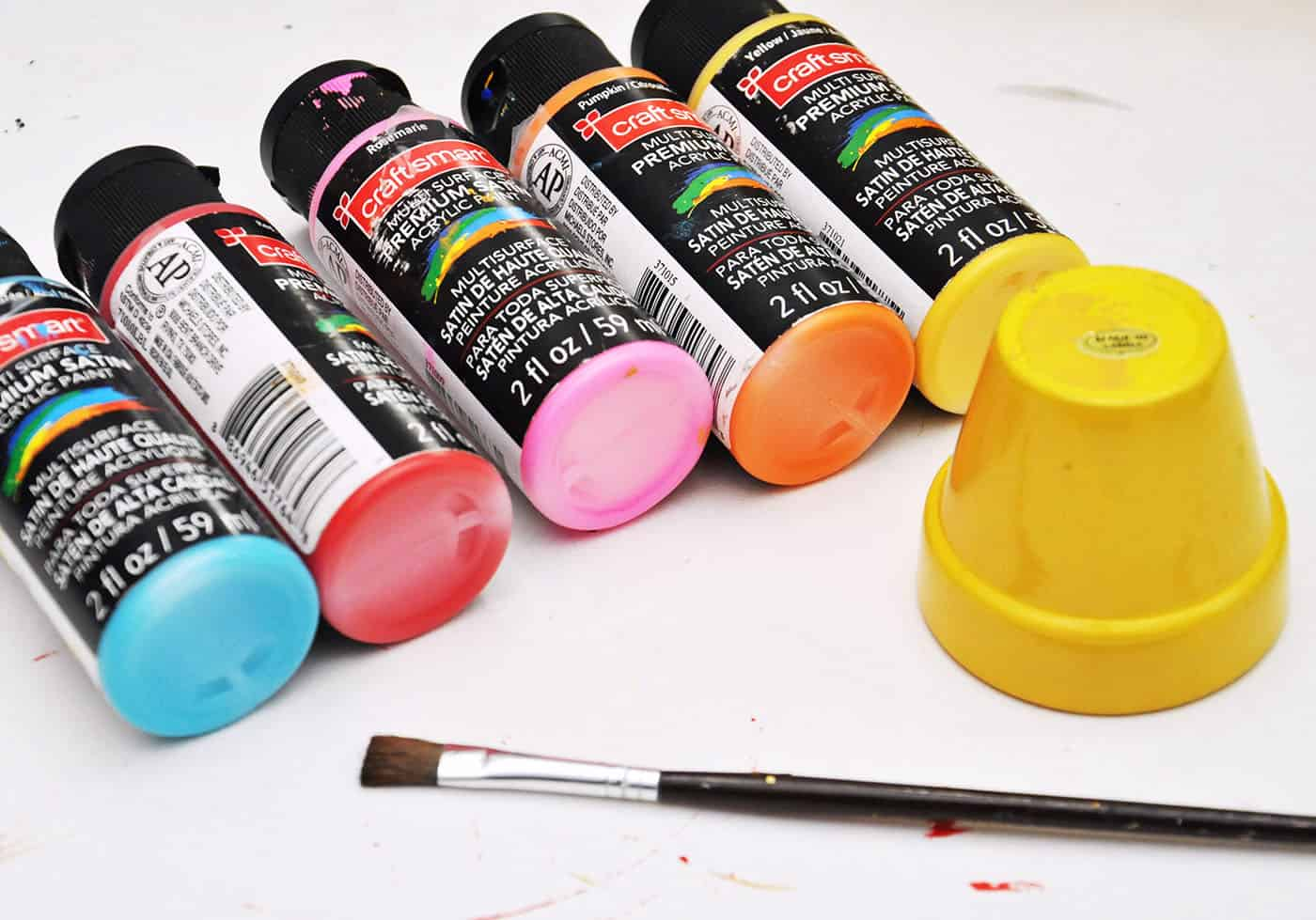 Various colors of craftsmart paint with a yellow painted flower pot