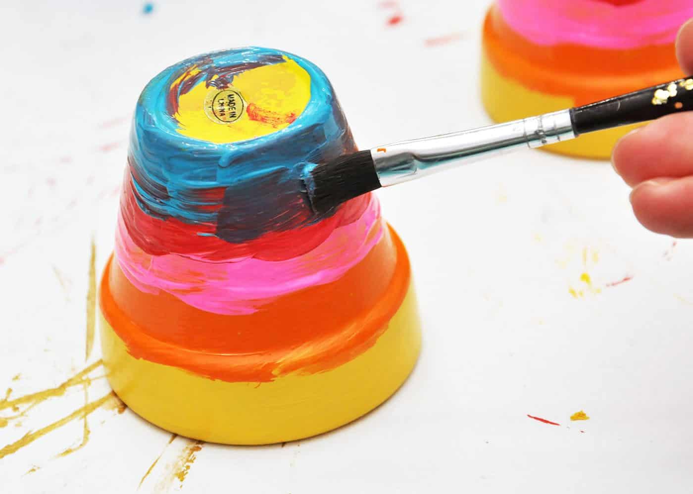 Painting a blue stripe on a rainbow pot