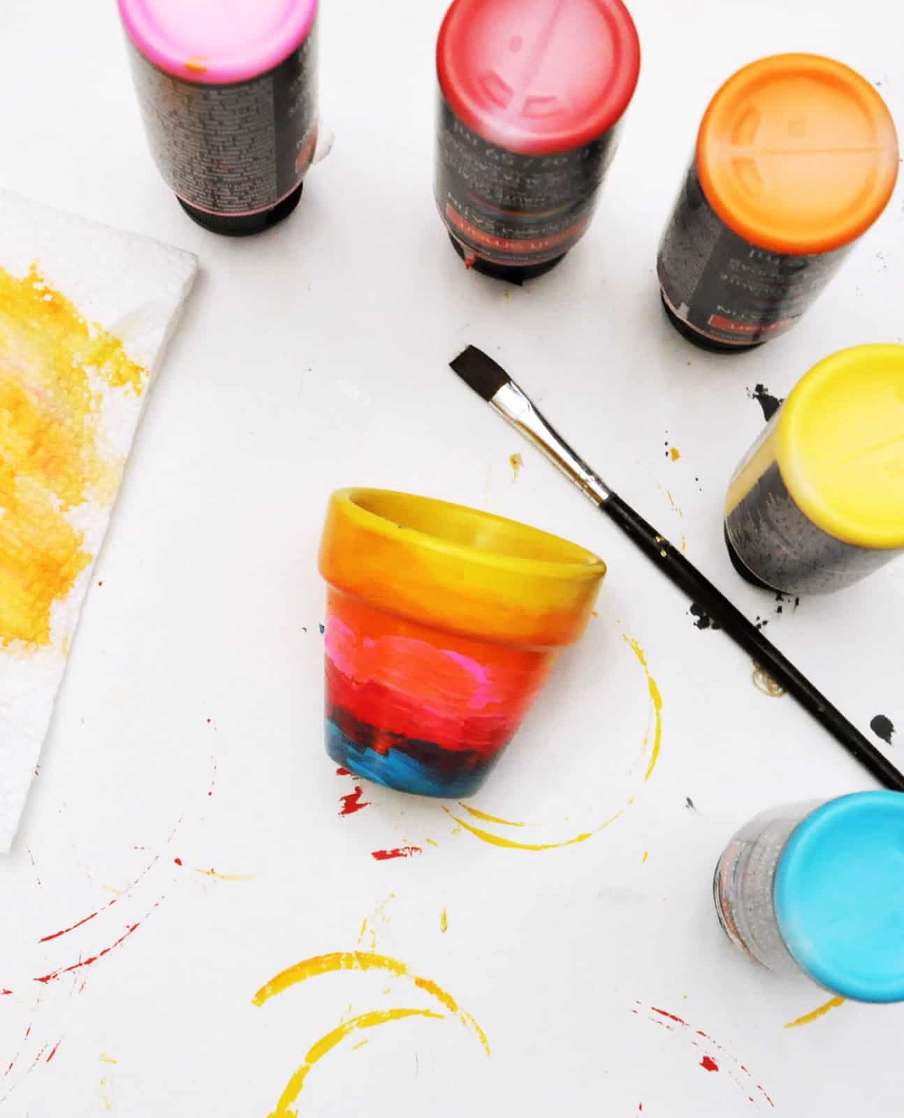 The bottom of four paint bottles and a painted pot with a paintbrush