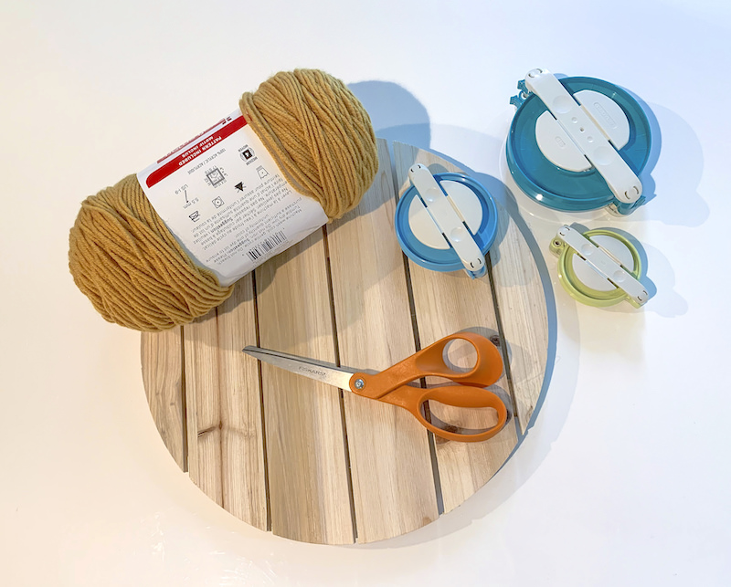 Wood plaque with scissors, pom pom makers, and yarn