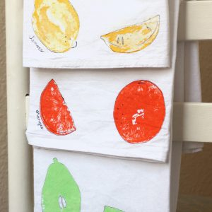 Fruit stamps on tea towels in yellow, orange, and mint