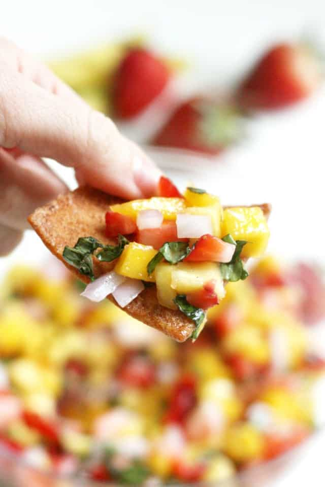 Easy mango salsa recipe with strawberries and basil on a tortilla chip