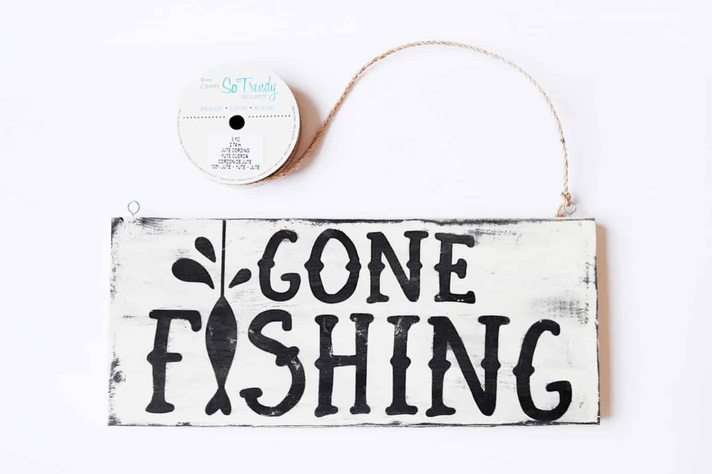 Tying jute to a gone fishing sign