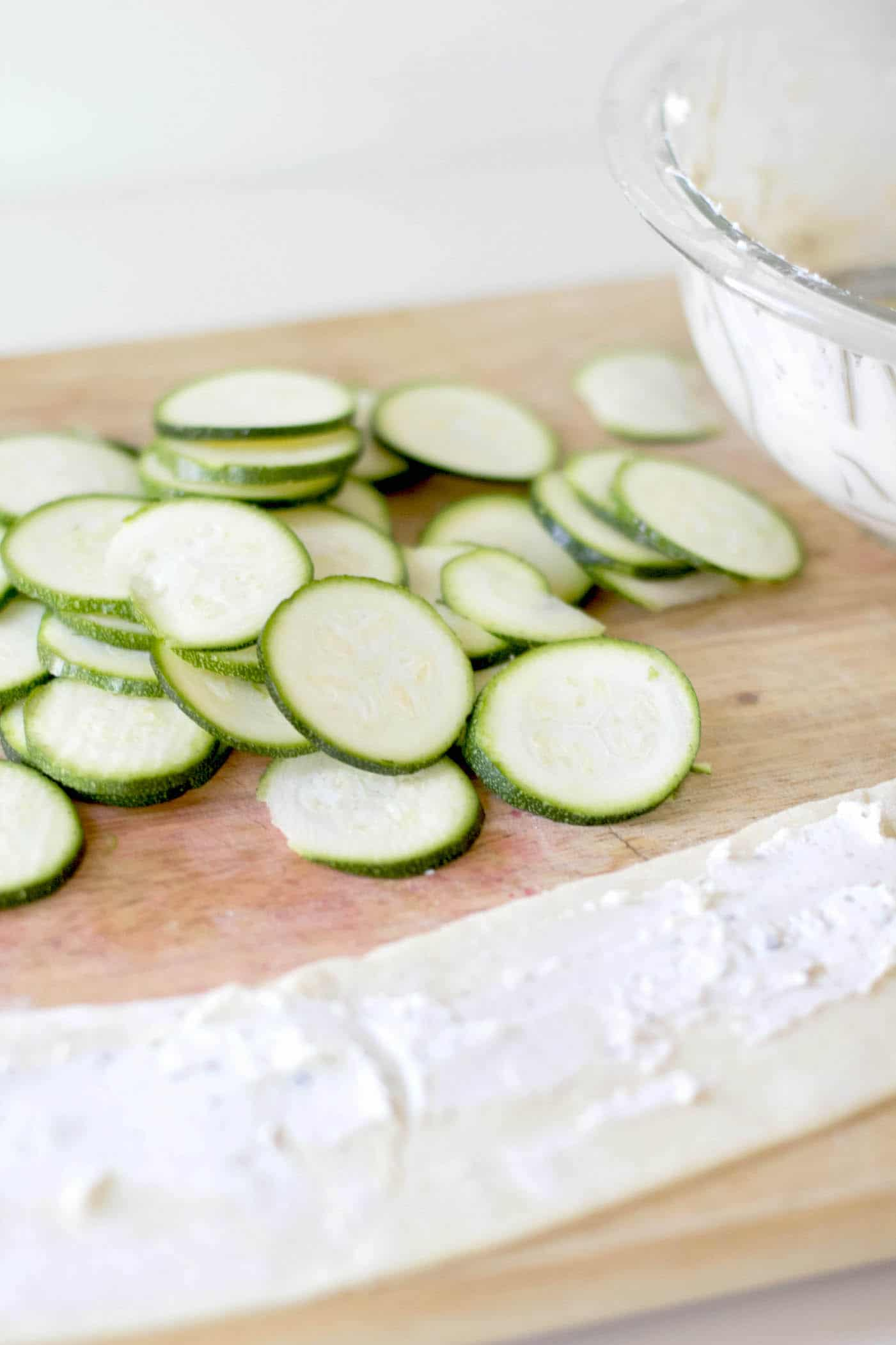 Puff pastry appetizer ingredients - zucchini sliced and dough rolled out with cream cheese