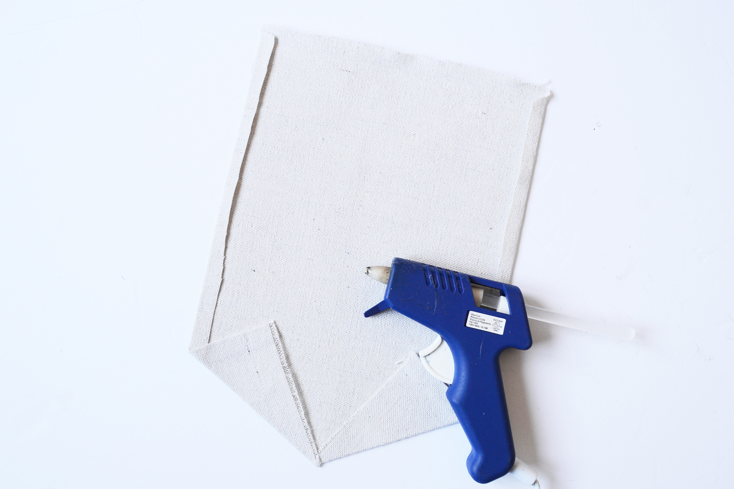 hot glue gun with a piece of canvas