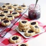 Lemon blueberry jam thumbprint cookies stacked on a plate