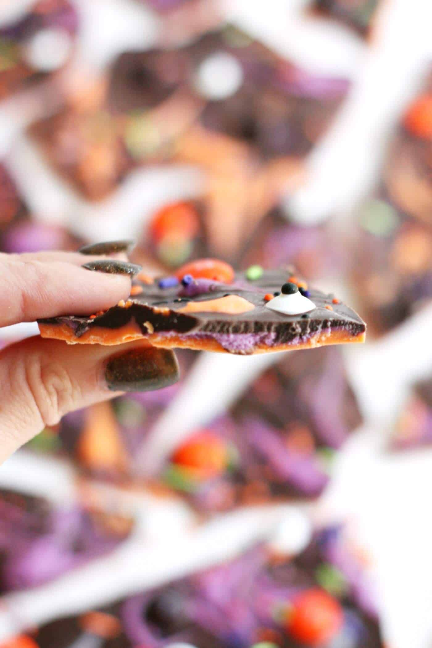 Holding a piece of spooky Halloween bark