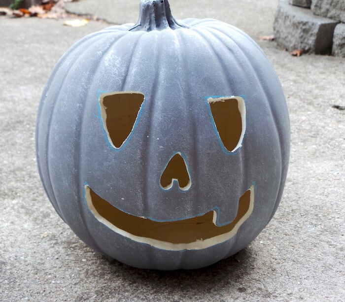 Concrete faux pumpkin with a face cut out