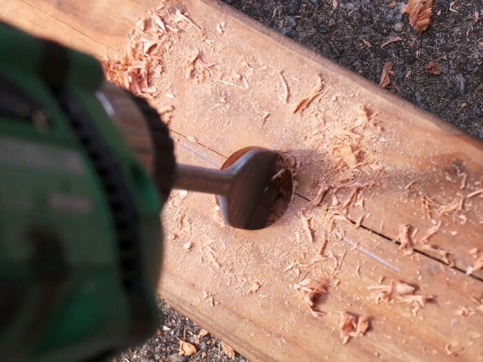Drilling with a spade bit into a piece of wood